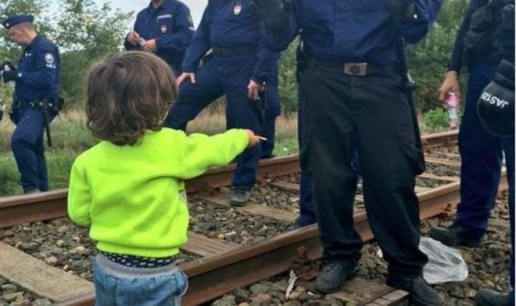 Προσφυγόπουλο προσφέρει ένα μπισκότο σε αστυνομικό στα σύνορα στην Ουγγαρία  - Κυρίως Φωτογραφία - Gallery - Video