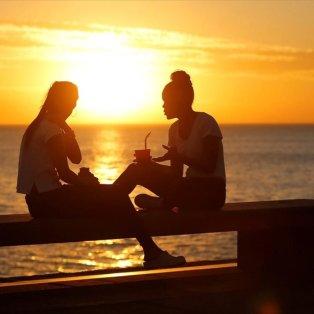 Δύο γυναίκες κουβεντιάζουν με φόντο το ηλιοβασίλεμα, στην προκυμαία του Μοντεβιδέο - Φωτογραφία: REUTERS / ANDRES STAPFF - Κυρίως Φωτογραφία - Gallery - Video