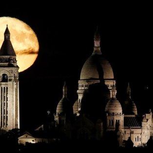 Το φεγγάρι διακρίνεται πίσω από τη Βασιλική της Ιερής Καρδιάς  Σακρέ Κερ στο Παρίσι  - Φωτογραφία: REUTERS / CHRISTIAN HARTMANN - Κυρίως Φωτογραφία - Gallery - Video